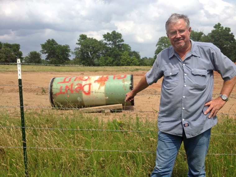 David Whitley stands near the dented pipe cutout he found on his property near Winnsboro.