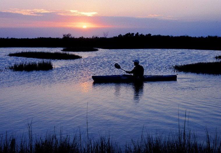 A man kayaks in the wetlands of Matagorda Bay Nature Park at sunset.