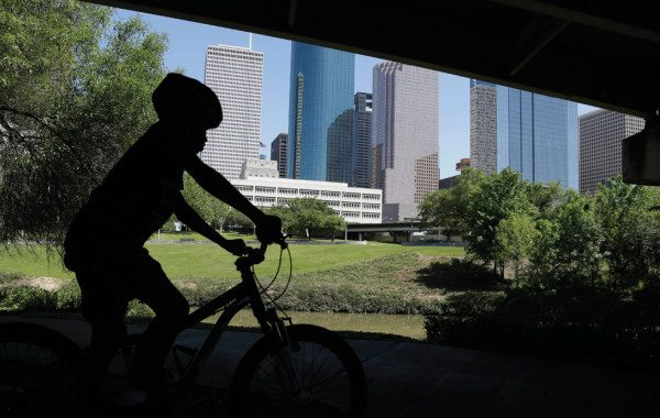 201507-boy-rides-bike-buffalo-bayou-ap-photo-pat-sullivan