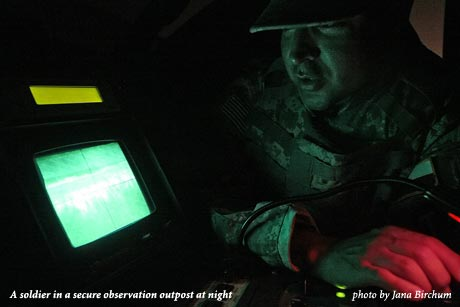 A soldier in a secure observation outpost at night, photo by Jana Birchum
