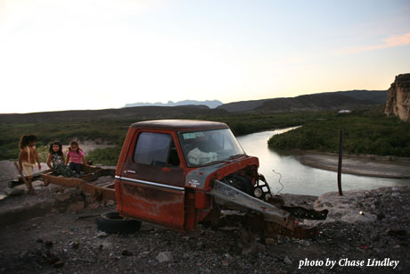 A broken down truck in front of a river, photo by Chase Lindley