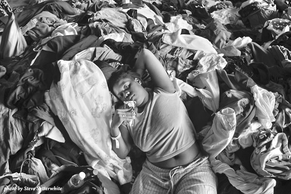 Young girl lying on a pile of clothes and other donated items