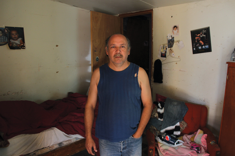 Baldemar Flores, 49, stands in the living room of his house in Cuevitas. His home lacks running water and has holes in its roof.