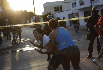 A woman is held back by another woman as she reacts to the killing of several people at a crime scene in Monterrey on August 29, 2012. Gunmen shot dead three men and a woman and left graffiti on a wall at the crime scene reading