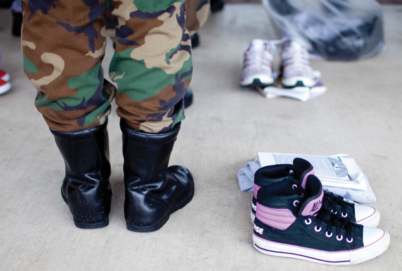 A uniformed Brownsville Academic Center student stands beside her sneakers and books.