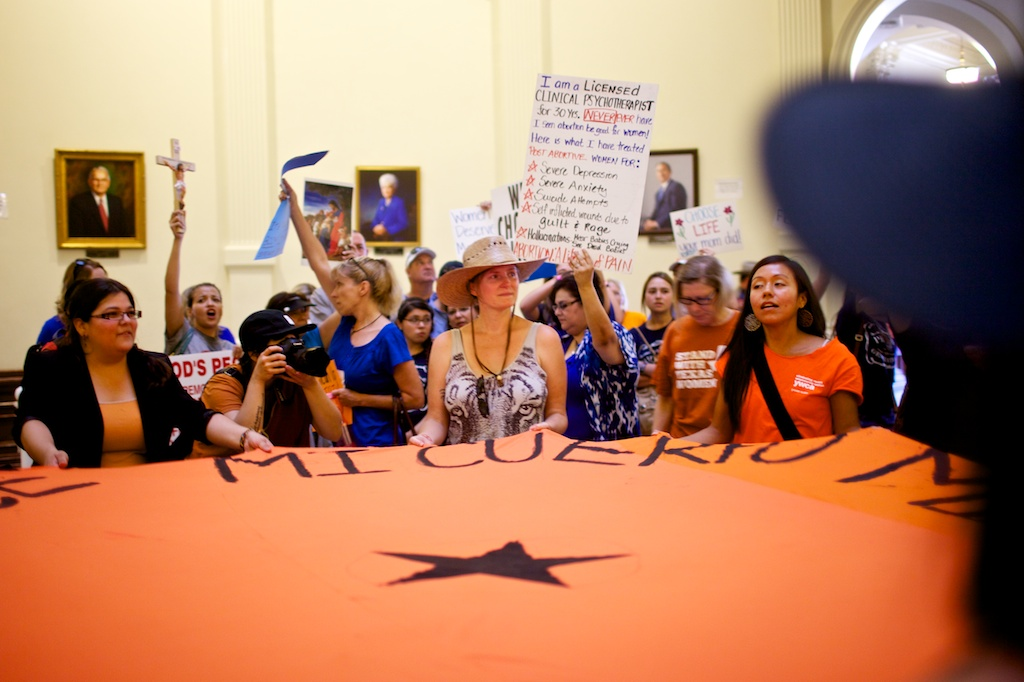 Pro-choice demonstrators wave a banner in the rotunda as an anti-abortion crowd holds crosses and signs behind them.