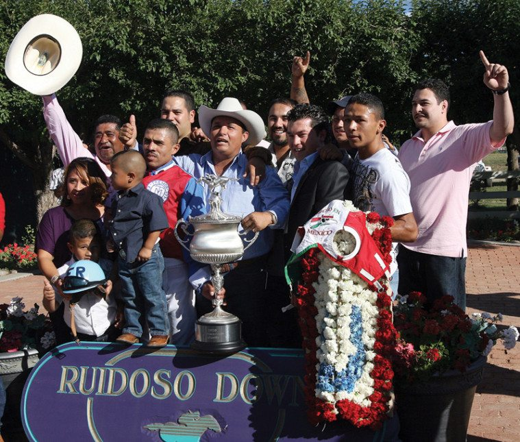Jose Trevino Morales, center, acknowledges the crowd after his horse, Mr. Piloto, won the All-American Futurity race at Ruidoso Downs, New Mexico, in September 2010.