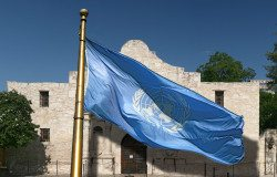 A United Nations flag looms large over the Alamo