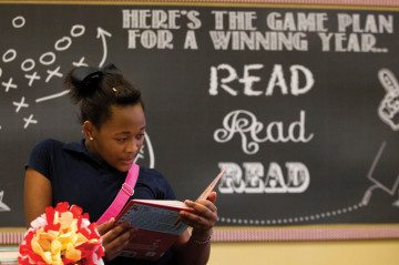 Meisha Washington reads a book in the newly reopened library at Houston's Hogg Middle School. The library had closed due to state budget cuts