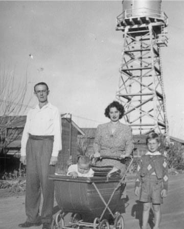 Mr. and Mrs. Werner Ulrich, Sr. and children walking down a street at the Crystal City Internment Camp, 1946.