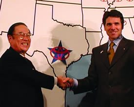 Rick Perry shakes hands with a Toyota executive in 2009