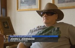 Giant chair owner John L. Johnson wearing a brimmed hat and sunglasses.