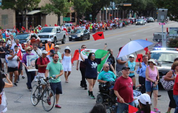 Hundreds of demonstrators walked four miles from St. Edward's University to the Texas Capitol, partially following in the footsteps of marching labor strikers in 1966.
