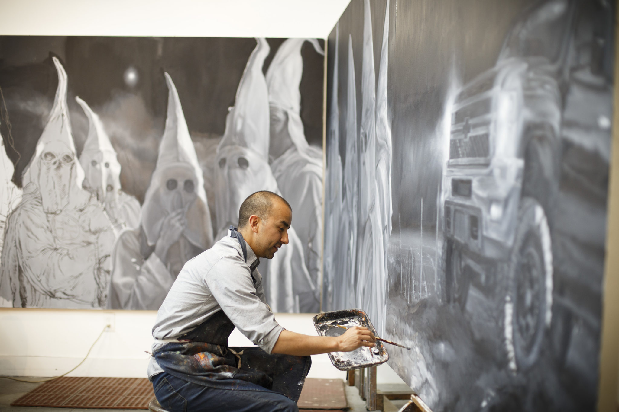 Mexican American artist Vincent Valdez works on his eight-panel painting of modern day klansmen in his studio in San Antonio.