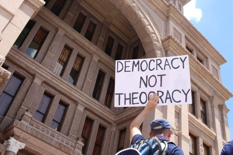 Activist holds sign on the South Steps of the Texas Capitol.