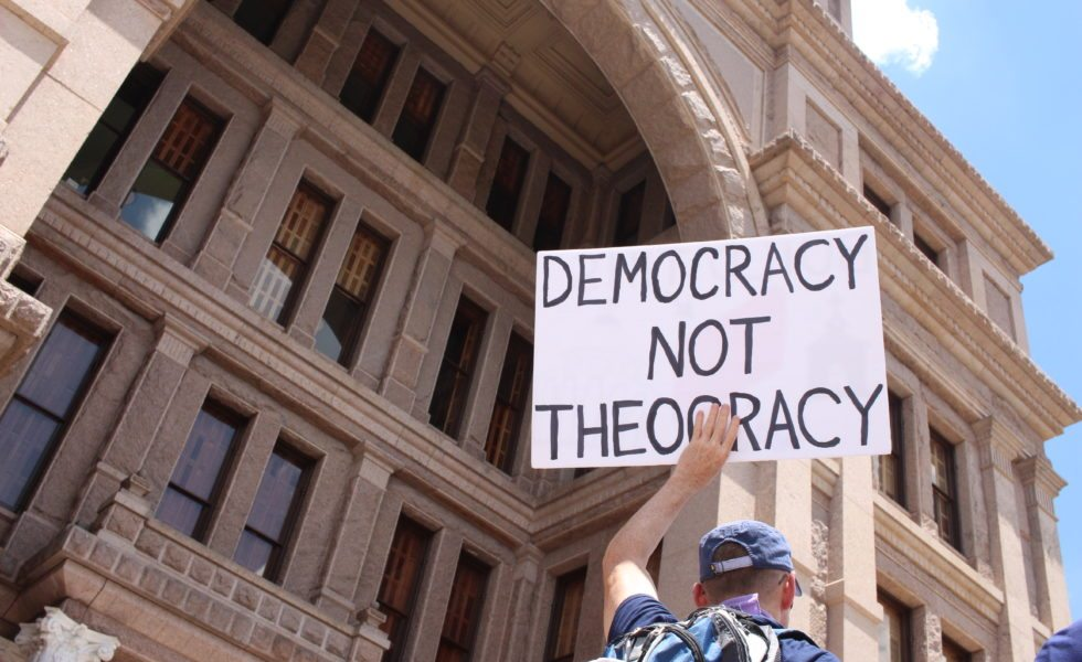 An activist holds sign on the South Steps of the Texas Capitol in 2017.