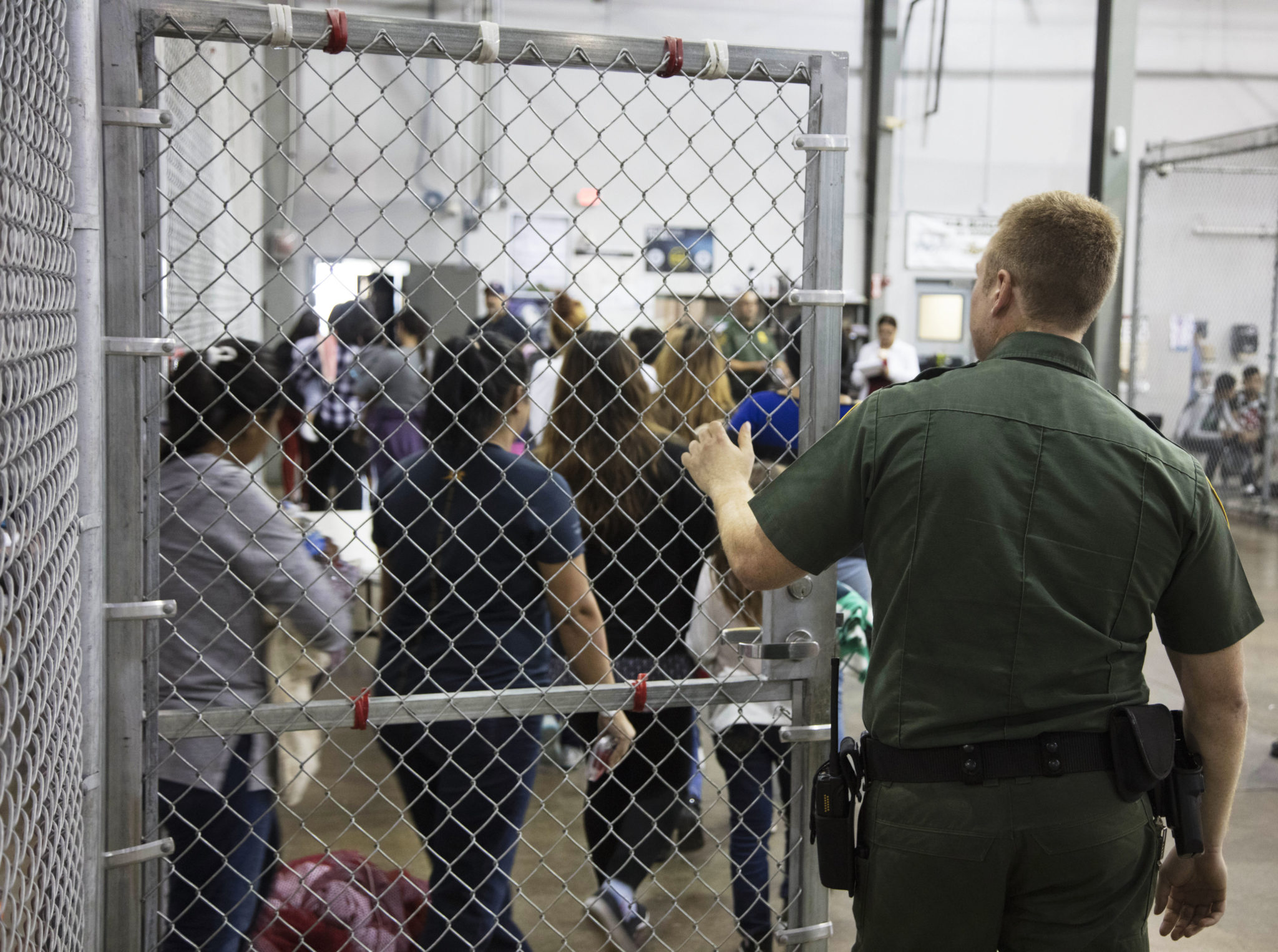 A Border Patrol agent watches as people who've been taken into custody stand in line at a facility in McAllen.