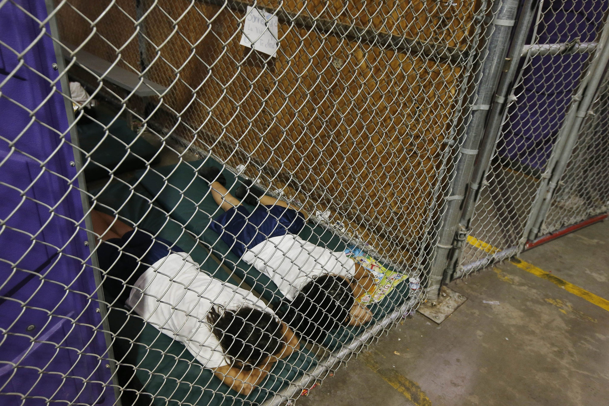 Two girls sleep in a holding cell at a Border Patrol facility in Nogales, Arizona.