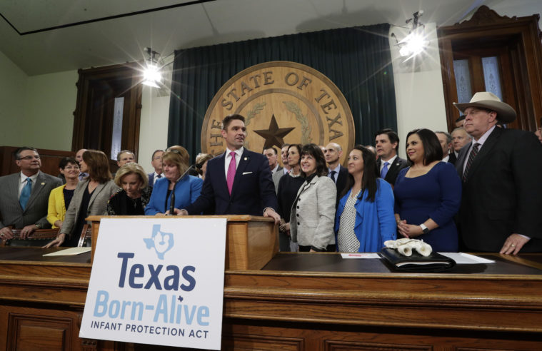 State Representative Jeff Leach, at podium, stands with fellow lawmakers and guests to talk about the Texas Born-Alive bill, Thursday, March 7, 2019.