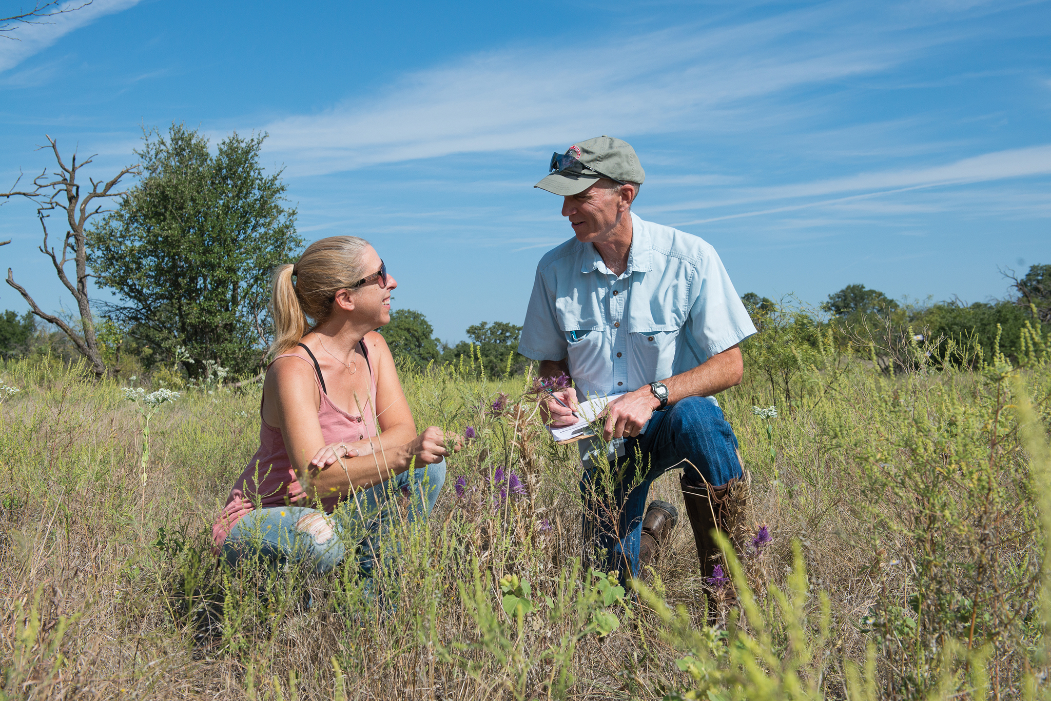 EDF's David Wolfe and Amy Greer check on the monarch butterfly habitat planted at Amy and George Greer's ranch.