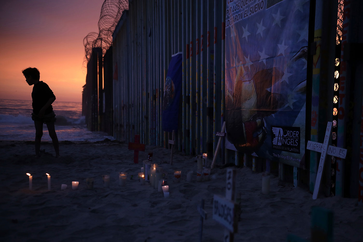 A youth stands by the border fence that separates Mexico from the United States.