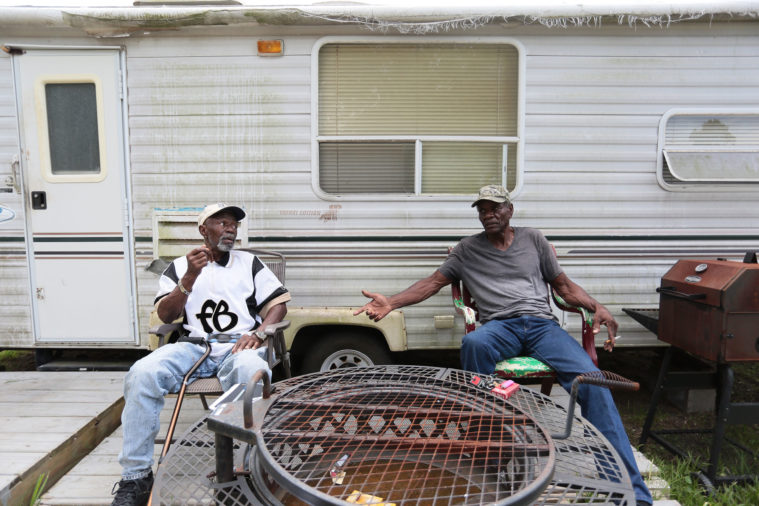 Henry Wilson, right, jacked up his storm-damaged house with his friend, Lester Owens, left. Wilson has lived in a trailer next to the house for the past two years.