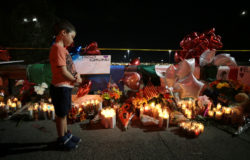A boy reacts as he looks at teddy bears left for children killed.