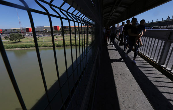 In this July 18, 2019, file photo, people walk back to Mexico on International Bridge 1 Las Americas, a legal port of entry which connects Laredo, Texas in the U.S. with Nuevo Laredo, Mexico. An unprecedented number of families have been coming to the southern border over the past year, straining government resources and resulting in dangerously overcrowded detention facilities. (AP Photo/Marco Ugarte, File)