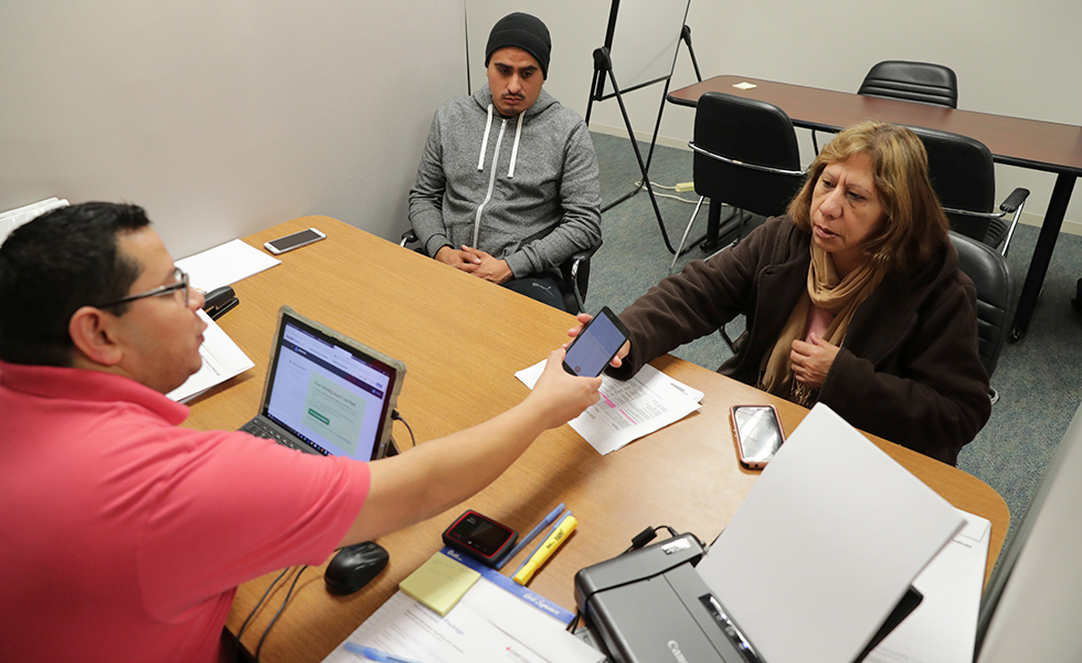 Community Council health care navigator Fidel Castro Hernandez, left, hands a Spanish help line phone to legal U.S. resident Maria Ana Pina, right, as she signs up for the Affordable Care Act with her son Roberto Pina in Dallas in 2017.