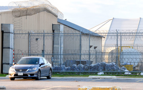In this March 7, 2015 file photo, trash bags are piled within the northern fence at the Willacy County Correctional Center as clean up begins at the emptied detention facility in Raymondville, Texas. Management and Training Corp. recently purchased the detention center that was shuttered after a 2015 inmate riot left it uninhabitable. (David Pike/Valley Morning Star via AP, File)