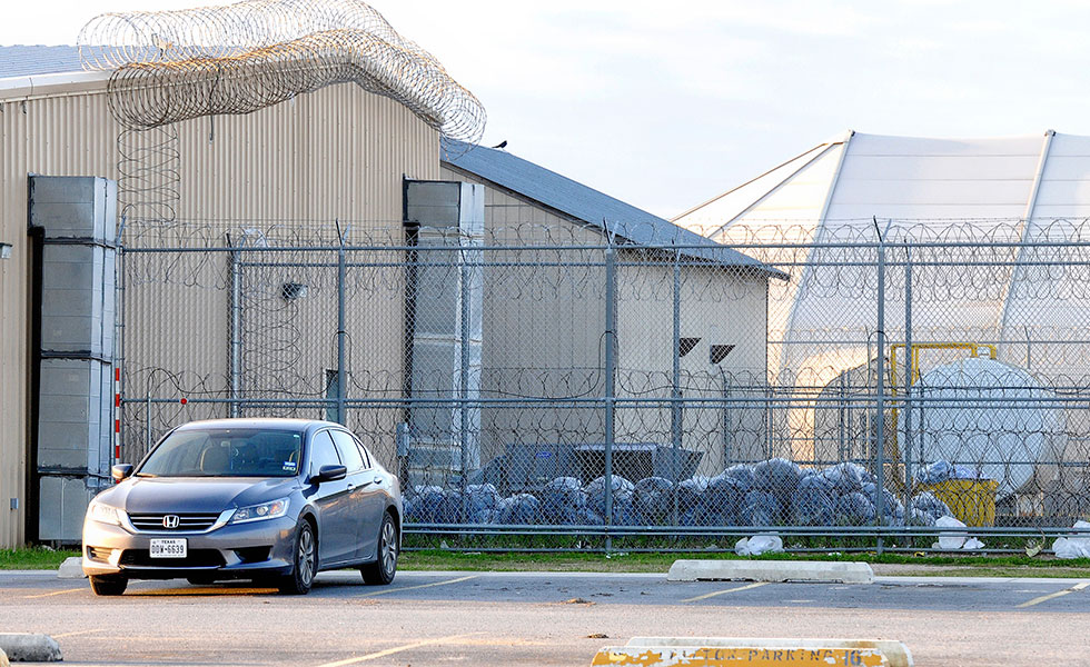 Trash bags are piled within the northern fence at the Willacy County Correctional Center as clean up begins at the emptied detention facility in Raymondville, Texas, in 2015.
