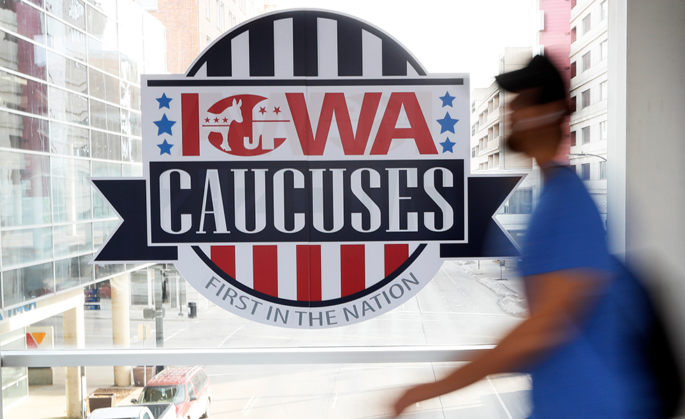 A pedestrian walks past a sign for the Iowa caucuses on downtown skywalk in Des Moines.
