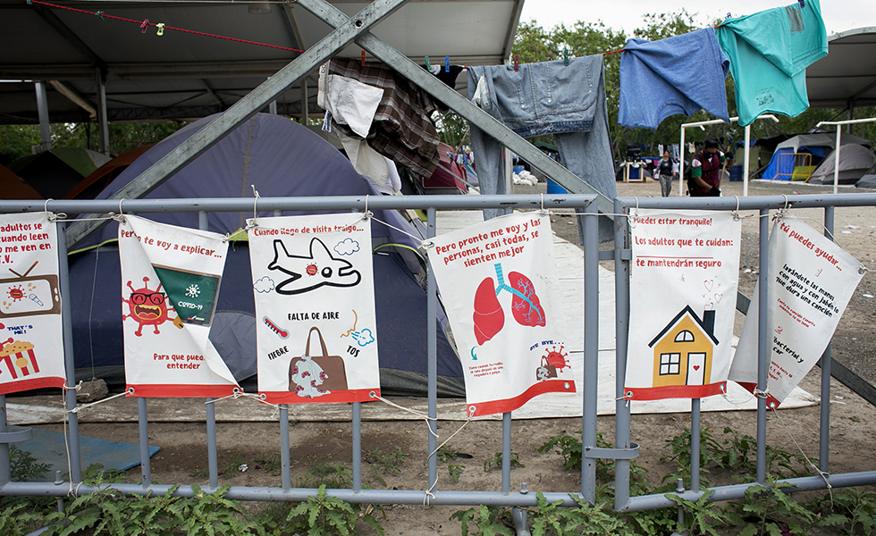 In this Wednesday, April 15, 2020, photo illustrated signs zip-tied to a gate provide simple facts about COVID-19 symptoms and ask people to stay calm at the migrant encampment outside El Puente Nuevo in Matamoros, Mexico.