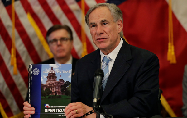 Texas Gov. Greg Abbott holds the Governor's Report to Reopen Texas book during a news conference where he announced he would relax some restrictions imposed on some businesses due to the COVID-19 pandemic, Monday, April 27, 2020, in Austin, Texas. (AP Photo/Eric Gay)