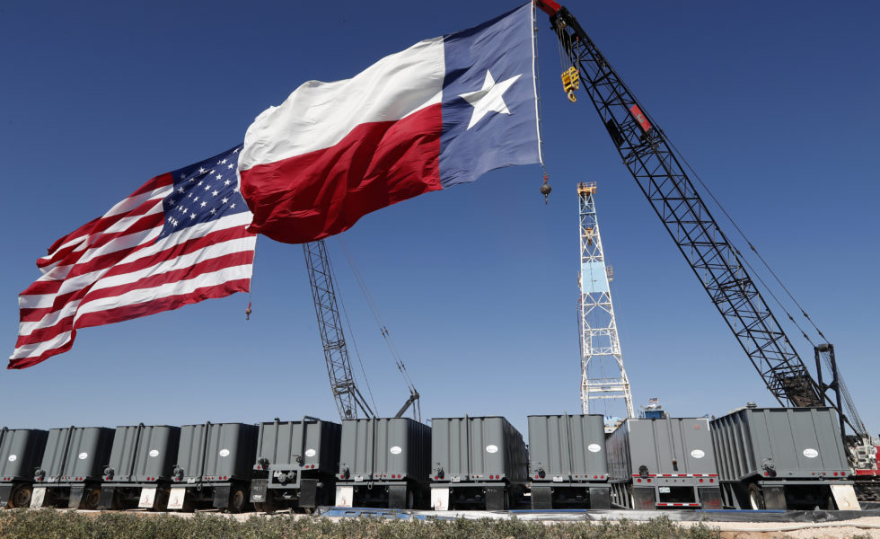 Flags fly from the tops of cranes near the site where President Donald Trump delivered remarks about American energy production during a visit to an oil rig in Midland.