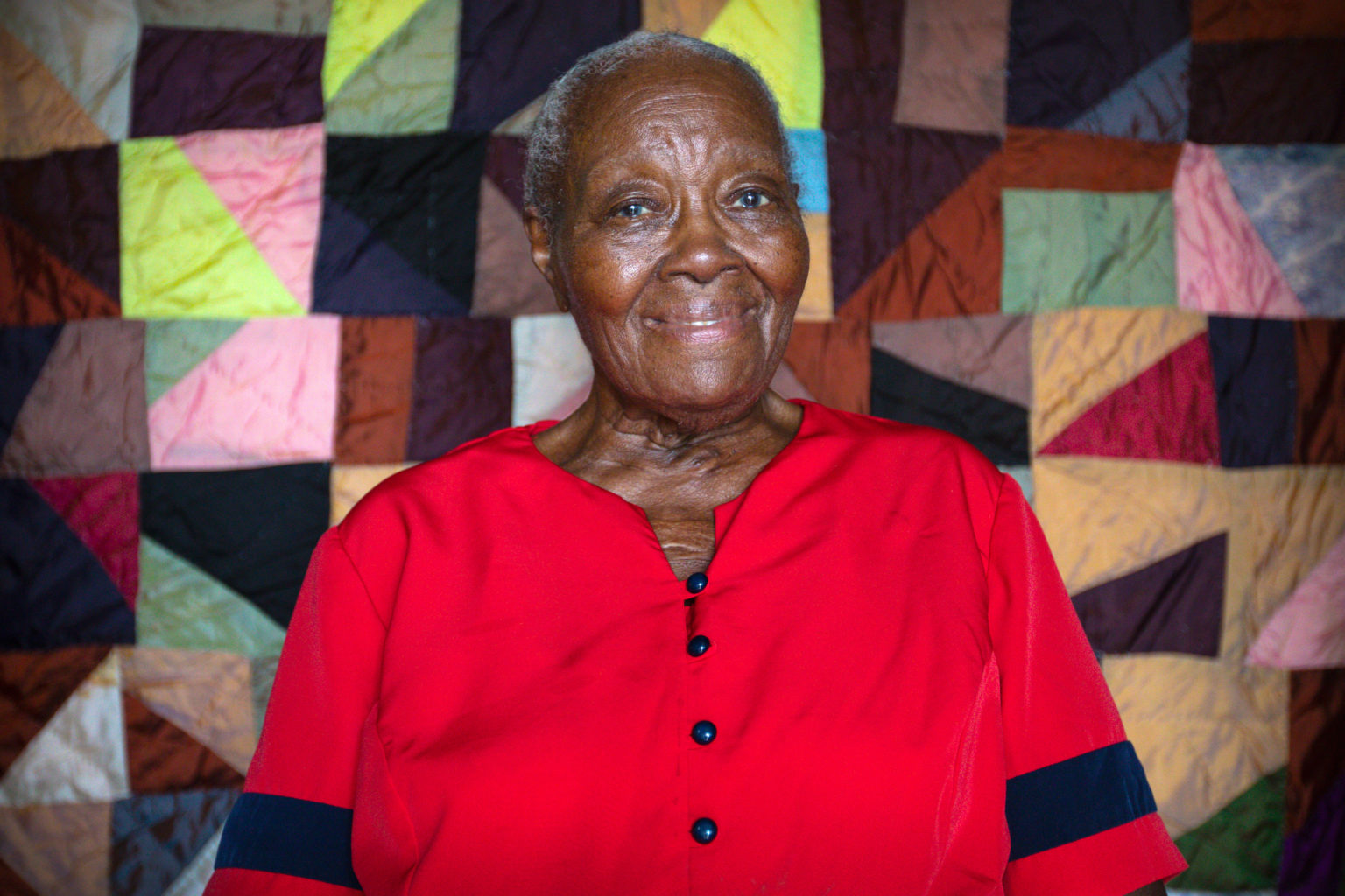 Laverne Brackens sits in front of one of her early quilts made with silk from Japan.