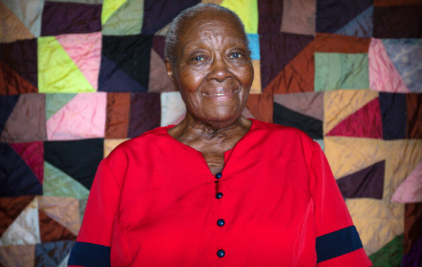 Laverne Brackens sits in front of one of her early quilts made with silk from Japan