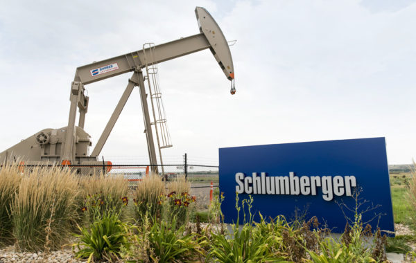 A logo sign and oil pump outside of a facility occupied by Schlumberger in Windsor, Colorado, on July 21, 2018. (Photo by Kristoffer Tripplaar/Sipa USA)(Sipa via AP Images)