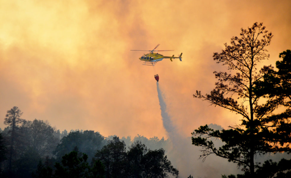 A helicopter drops water on a forest fire near Jefferson in East Texas in September 2011.